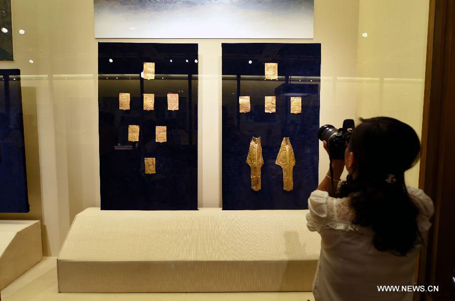 A woman visits a public exhibition of Chinese cultural relics returned by French  private collectors, at Gansu Provincial Museum in Lanzhou, capital of northwest  China's Gansu Province, July 20, 2015 Photo Credit: Xinhua/Fan Peishen.