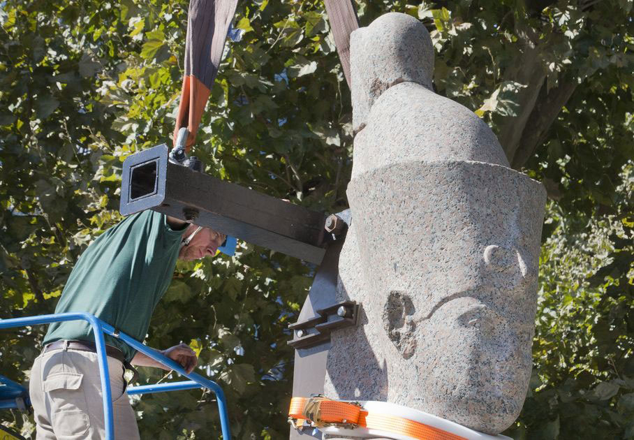 A worker sets up a statue of an unnamed king dating from the Ptolemy era, made of pink granite and measuring 5 meters and weighing 5.5 tons in Paris, Friday Aug 21, 2015. Photo Credit: AP Photo/Jacques Brinon.