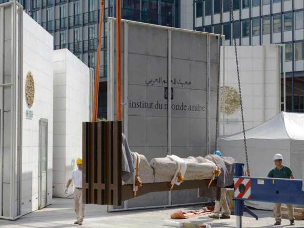 Workers help carrying one of three statues erected on the square of the Arab World Institute in Paris, on August 21, 2015. Photo Credit: HUGO MATHY/AFP/Getty Images.