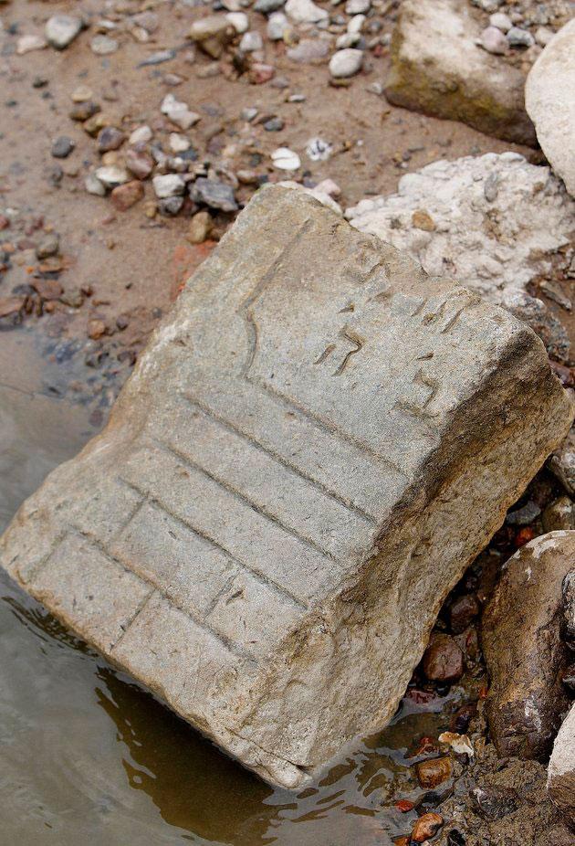 A fragment of a Jewish tombstone lies exposed along the Vistula River in Warsaw, Poland, on Aug. 25, 2015. Photo Credit: CZAREK SOKOLOWSKI/AP.