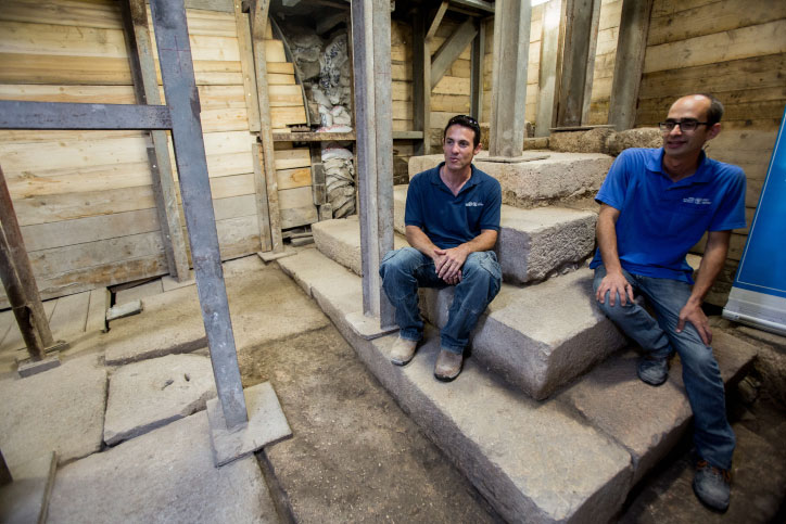 Israel Antiquity Authority archaeologists sit on the stair structure found on a street ascending the Siloam Pool to Jerusalem's Old City, on August 31, 2015. Photo Credit: Yonatan Sindel/Flash90/Times of Israel.