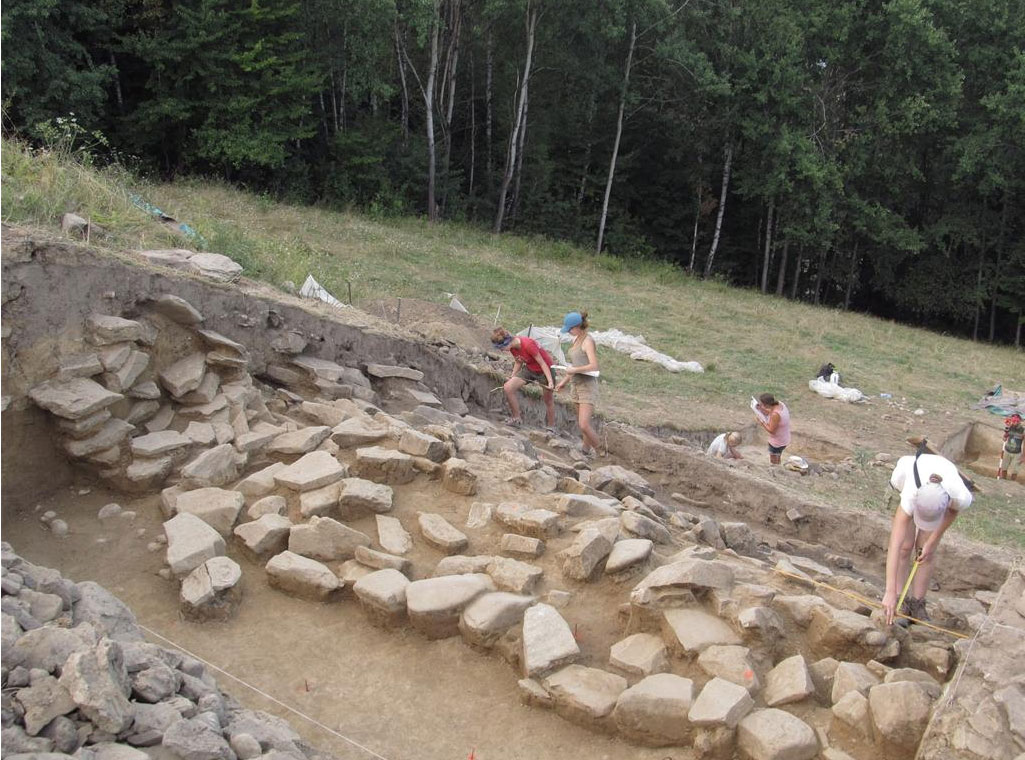 View of the northern part of the archaeological excavation in mid-August. Retaining wall from the Early Bronze Age is visible on the cross section of the trench, in the bottom of the trench a line of rocks forming the lowest layer of the wall. Photo by M.S. Przybyła.