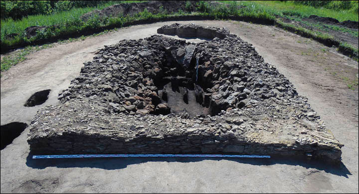 A view of the burial chamber, a hole in the ground, with a stone wall built around it, covered with logs. Photo Credit: Pavel German.