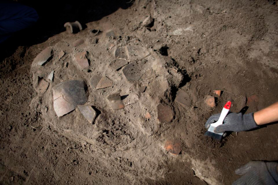 A worker clears the area around broken pottery lying in situ at the Zultepec-Tecoaque  archaeological site in Tlaxcala state, Mexico, Thursday, Oct. 8, 2015. The inhabitants  of the Aztec-allied town are known as Texcocanos or Acolhuas. Photo Credit: AP/Rebecca Blackwell.