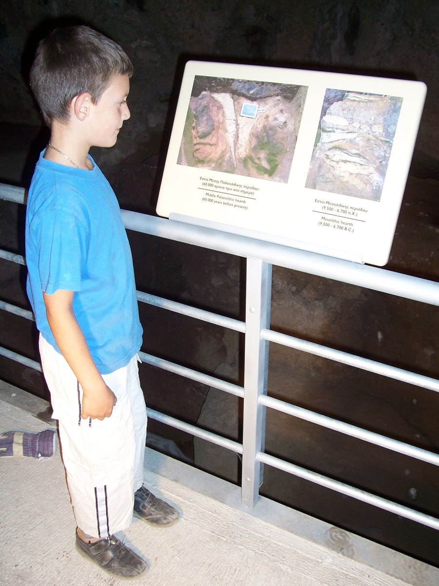 Fig. 4. A schoolboy reads from an information board inside the cave.