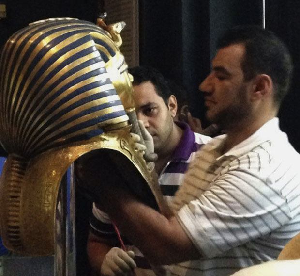 A man glues the beard part of King Tutankhamun's mask back on at the Egyptian Museum in Cairo, Egypt.