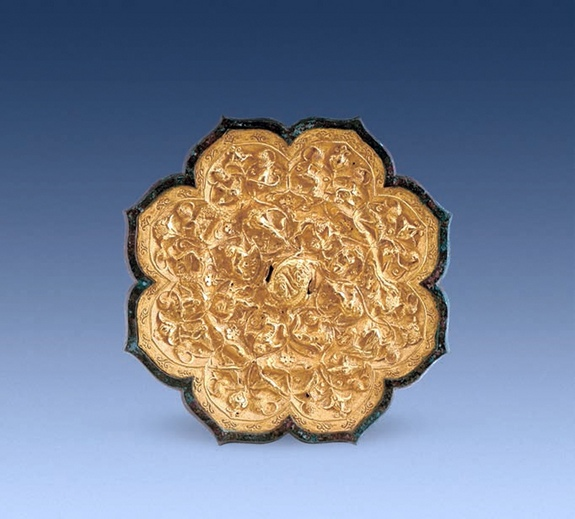 A mirror with a gold plaque on the back, in the shape of a flower petal, decorated with images of animals and grapes. It was buried with Lady Pei. Photo Credit: Chinese Cultural Relics.