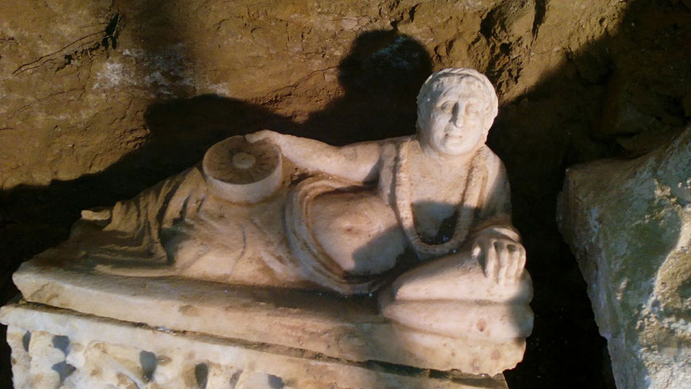 One of the reclining figures on the lid of an  urn. Photo Credit: Superintendency of Archaeology of Umbria.