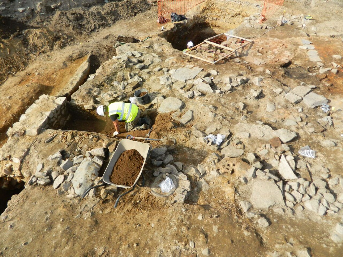 Archaeologists painstakingly excavate the remains of a late Roman building.  Part of a wall can be seen to the left whilst pieces of stone flooring survive to the right [Credit: University of Leicester]