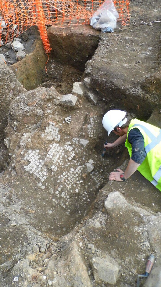 The remains of a Roman mosaic pavement is carefully uncovered. After the  building was demolished, the pavement has broken and collapsed down into  one of the empty foundation trenches [Credit: University of Leicester]