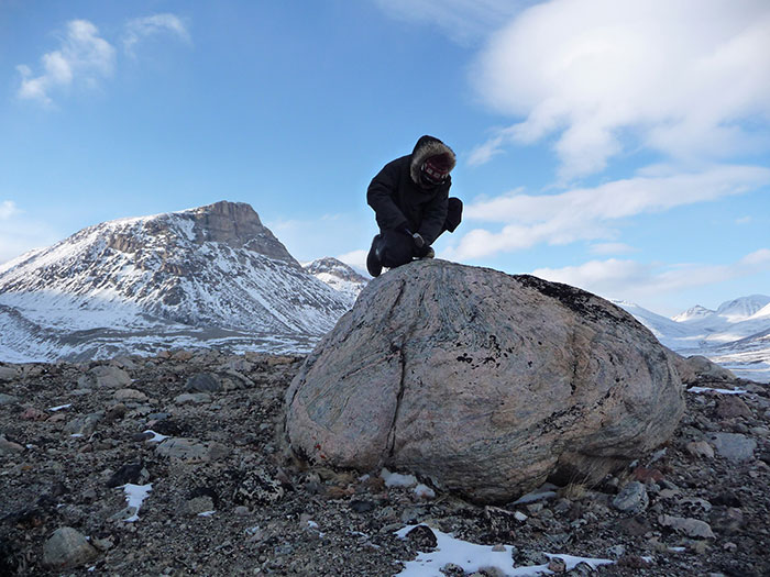 In Baffin Island's Naqsaq Valley, University at Buffalo geologist Jason Briner samples a boulder left by a glacier around the time of early Viking settlement. Measurements of chemical isotopes within the rock suggest settlers in neighboring Greenland faced cold weather. Photo Credit: Nicolás Young.