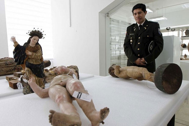A police officer stands near some of the restituted objects during a news conference at Ecuador's National Cultural Heritage Institute in Quito. Photo Credit: The Art Newspaper.