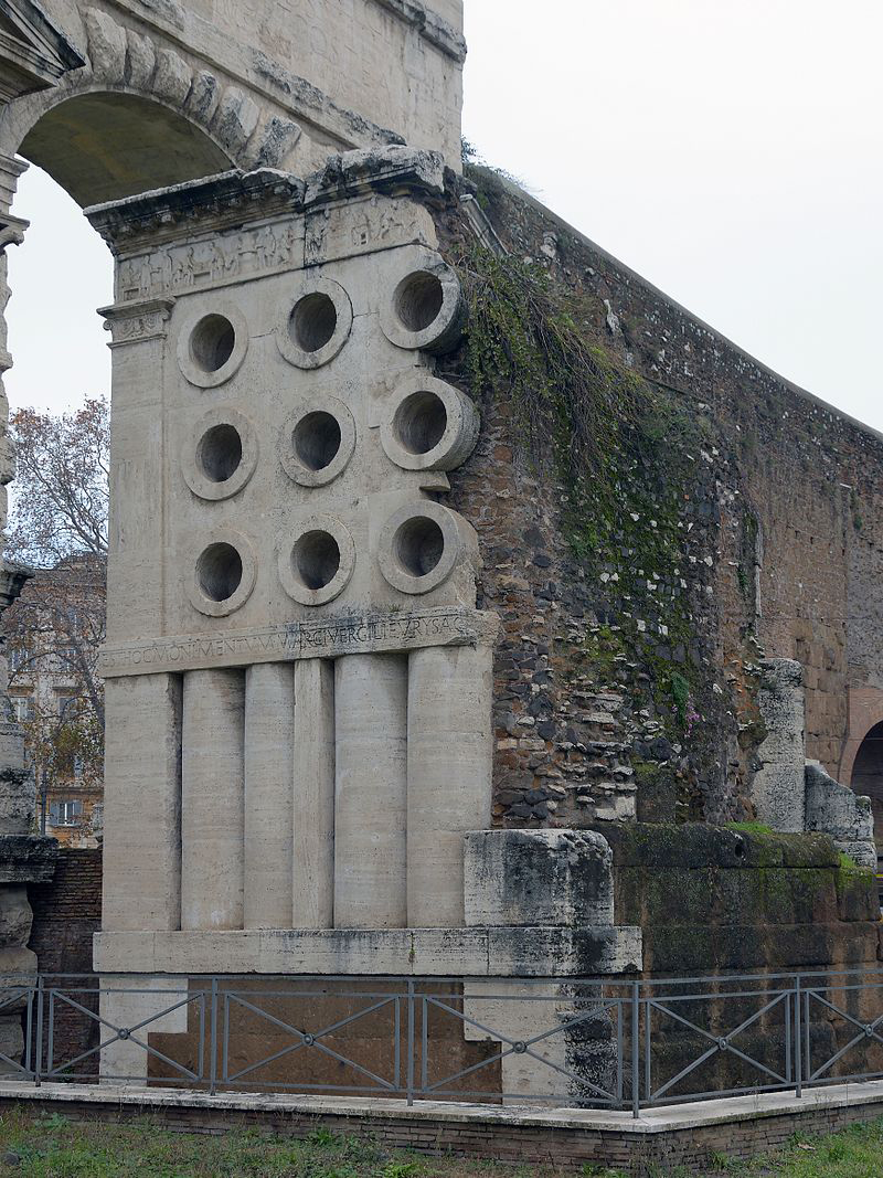 South facade of the Tomb of Eurysaces outside Porta Maggiore, with the Aqua Claudia behind; the nine cylinders may represent grain measures or mixing vessels. Credit: Livioandronico2013  Wikimedia Commons CC BY-SA 4.0