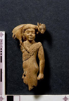 The ivory statuette is depicting a standing man holding a deer or gazelle over his shoulders.
