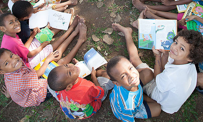 Children at Buk bilong Pikinini (books for children) which is an independent not-for-profit organisation based in Port Moresby, Papua New Guinea, which aims to establish children's libraries and foster a love of reading and learning. Source: Wikimedia Commons