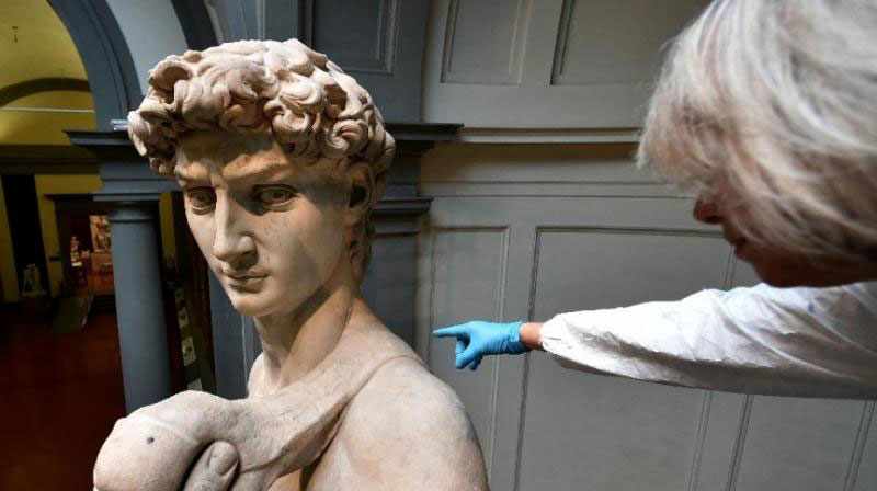 An Italian restorer from the Friends of Florence Association cleans Michelangelo's David, one of the world's most famous statues, at the Galleria dell'Accademia in Florence on February 29, 2016. Photo Credit: AFP/Alberto Pizzoli.