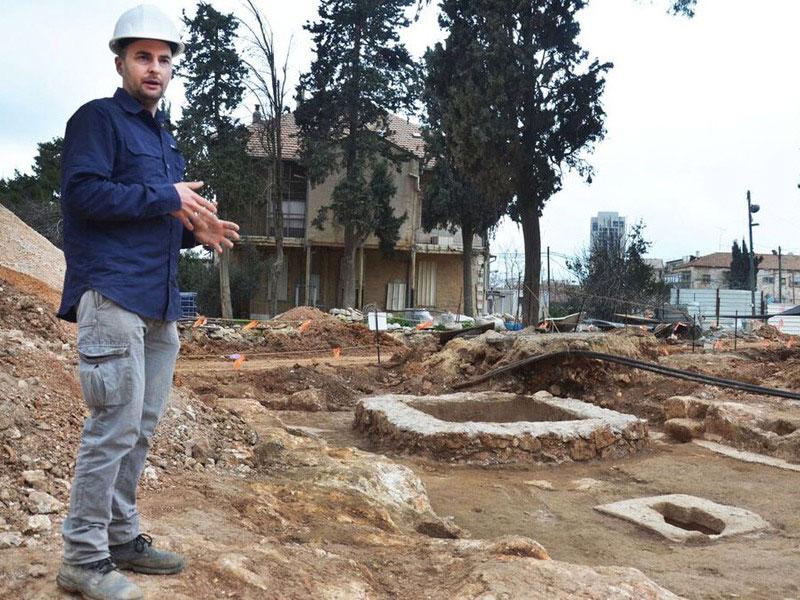 Alex Wiegmann, excavation director, views winepress uncovered  in Schneller Compound. Photo Credit: IAA/Archaeology News Network.