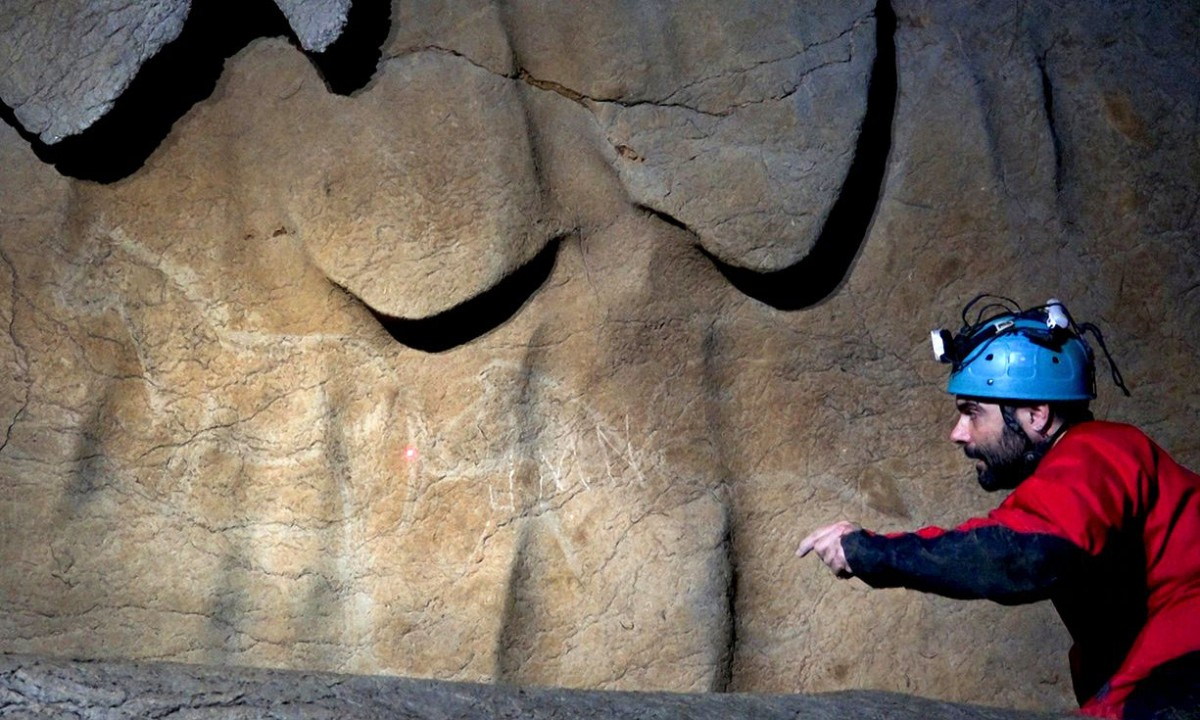 Archaeologist Diego Garate looking at cave paintings representing horses in the Atxurra cave. Photo Credit: AFP/Getty Images/The Guardian.