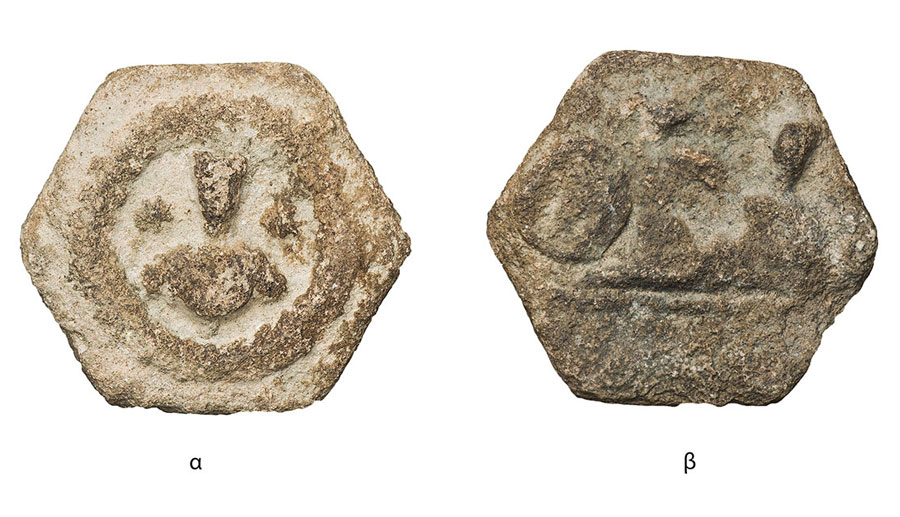 Fig. 1. Hexagonal shaped token. 26 millimeters Side a: Frontal bust of priest. Side b: Two human figures. Possibly a banquet scene. On the left, the impression of a private stamp can be distinguished. An inscription is on the exergue (Numismatic Museum 214/2005). Epigraphic and Numismatic Museum, Athens. ©The copyright belongs to the Ministry of Culture and Sports.