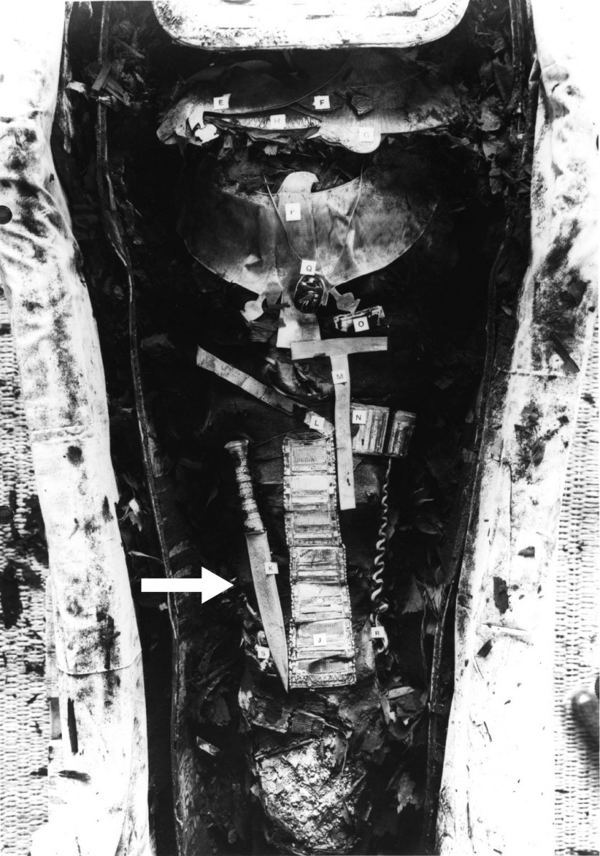 Black and white picture of Tutankhamun mummy showing the iron dagger placed on the right thigh (arrowed). Photo Credit: Griffith Institute, University of Oxford.