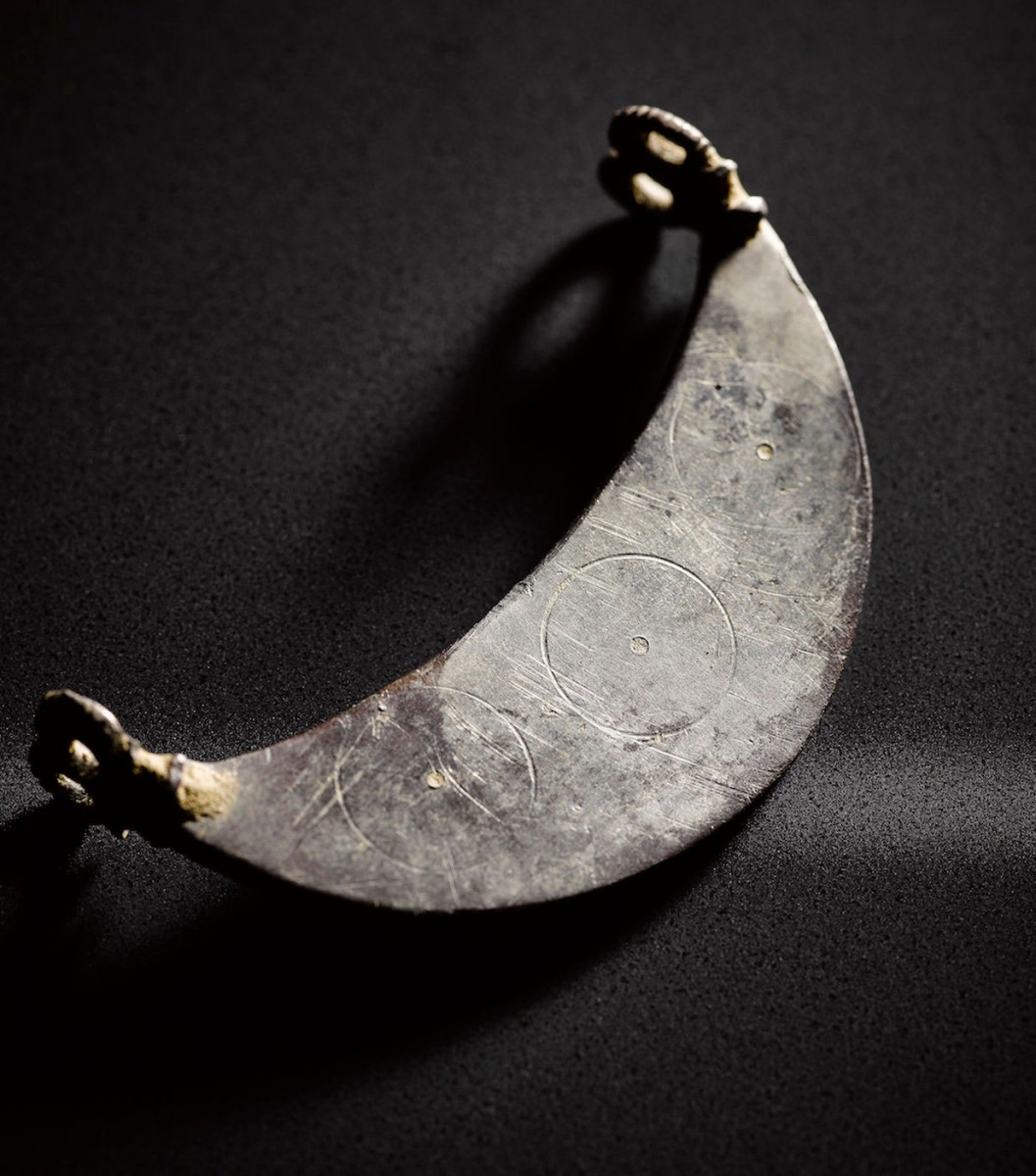 A crescent-shaped pendant that has two double loops. Photo Credit: Live Science.