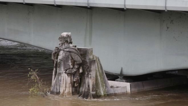 The water has covered the feet of the Zouave statue. In 1910 floods the water had reached its shoulders. Photo Credit: REUTERS/BBC.