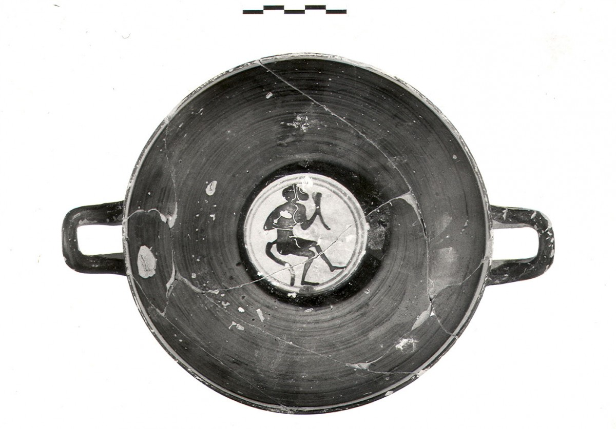 Fig. 4c. Example of imported grave offerings from Attica (1st quarter of 5th c B.C.). Black figure kylix K.3555 with a scene from the Dionysiac cycle. Depicted in the centre is a satyr with a donkey's head holding a horn, from Jar LXI. (Photographic archive of the 14th Ephorate of Prehistoric and Classical Antiquities)