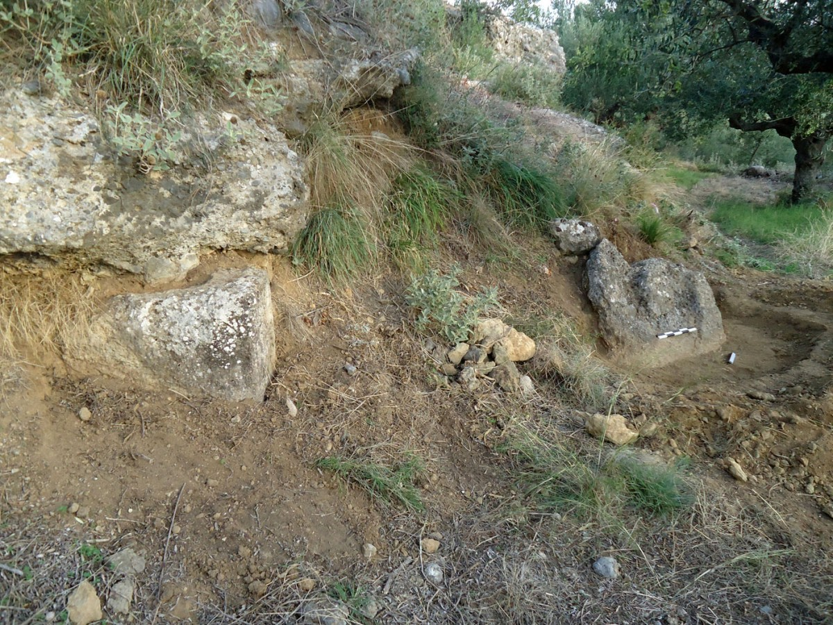 "Fig. 6. ""Hellenika"" in Thouria. Property of N. Krikkas. The carved natural rock of the oil press. On the left end is part of the isodomic wall of the ancient building."