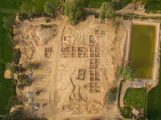This photograph, taken from a drone, shows the key trench, the main trenches on the mound, the grave of Peer Baba (which stands separately on the mound) and a concrete tank with water to irrigate the wheat fields that surround the mound at 4MSR. Photo Credit:ASI/Frontline.