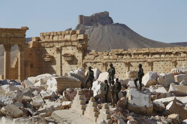 Syrian army soldiers stand on the ruins of the Temple of Bel in the historic city of Palmyra, in Homs Governorate,  Syria this April 1, 2016. Photo Credit: Reuters/Omar Sanadiki.