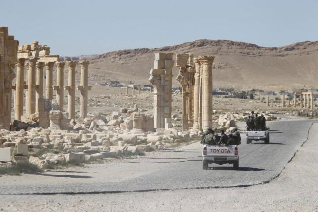 Syrian army soldiers drive past the Arch of Triumph in the historic city of Palmyra, in Homs Governorate,  Syria April 1, 2016. Photo Credit: Reuters/Omar Sanadiki.