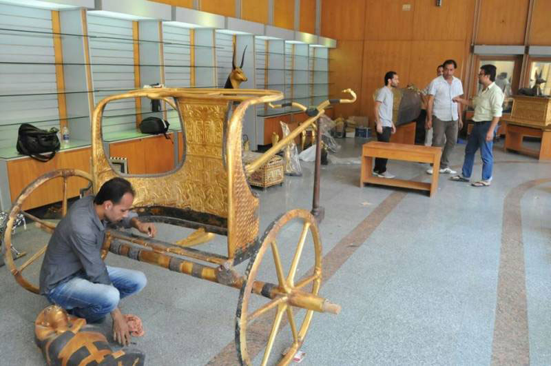 Craftsmen put the finishing touches to a replica chariot put on display by the Antiquities Ministry. Photo Credit: Egypt Independent.