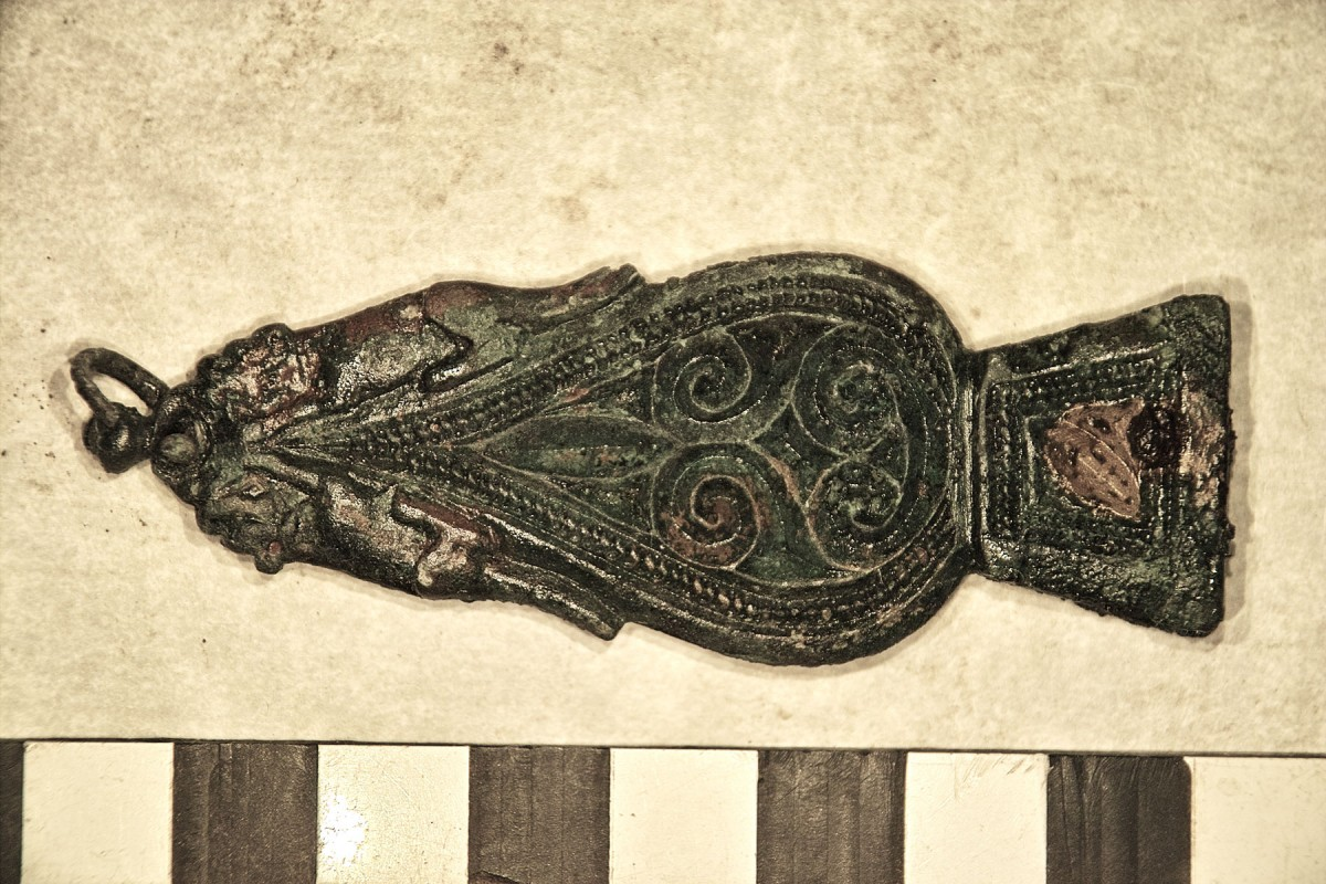 Fig. 6. The strap end is decorated with crouching dogs on either side of its tapered end.