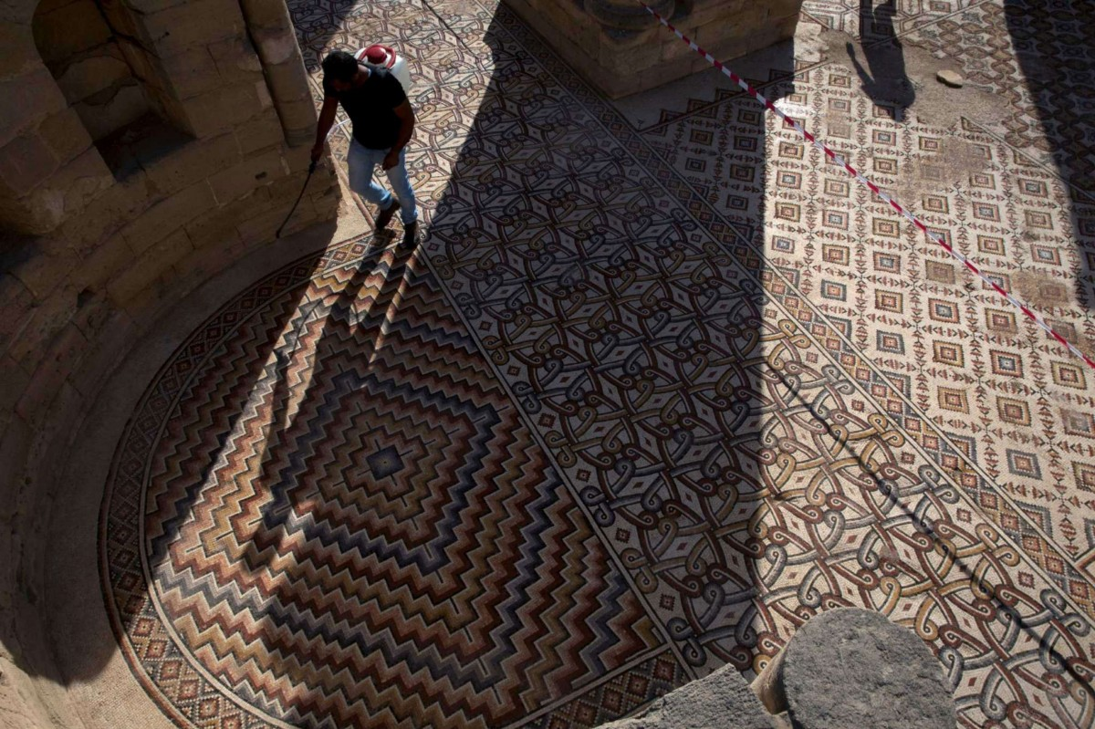 A labourer from the Palestinian Ministry of Tourism and Antiquities works at the site of the mosaic ahead of the opening ceremony at the Islamic archaeological site of Hisham Palace. Photo Credit: AP Photo/Nasser Nasser/Phys Org.
