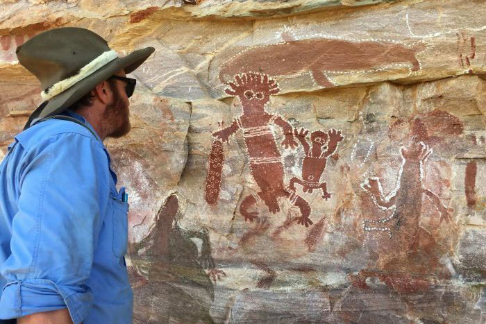 Survey pilot Nick Sundblom examines rock art found near Forrest River. Photo Credit: Erin Parke/ABC News.
