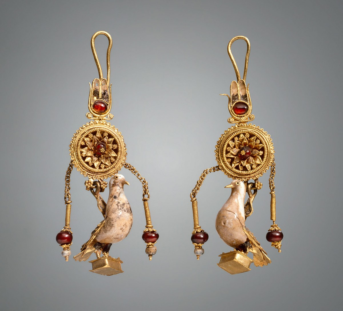 Earrings with pendants in the form of a dove. 2nd c. BC. Gold, hessonite, glass. Height 6.3/6.5 cm. Credit: State Hermitage Museum, St Petersburg.