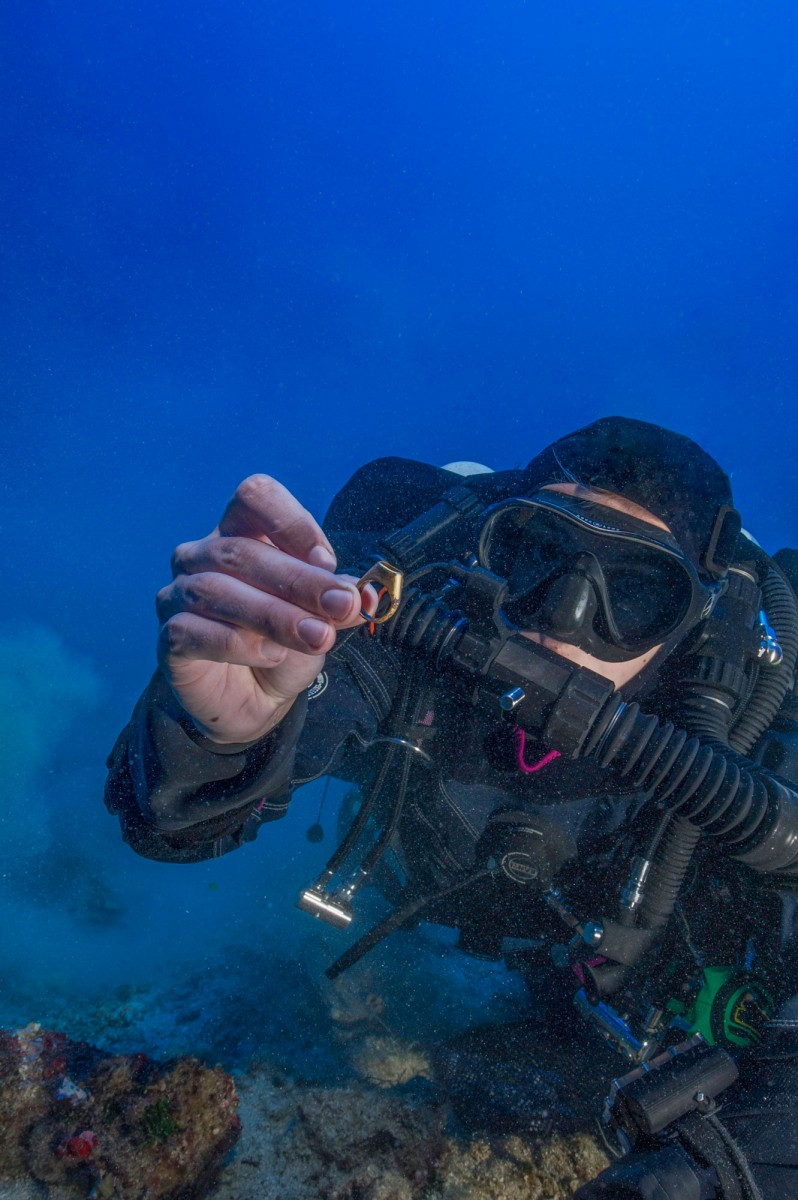 Gemma Smith, diver of the research team and the first woman to dive to the spot of the Antikythera Shipwreck, holding the gold ring.