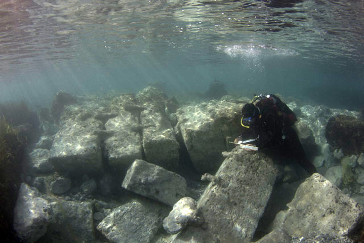 An archaeologist is drawing a block in the area of the Entrance Channel. The metal rivets are preserved. Photo credit: V. Tsiairis, 2016.