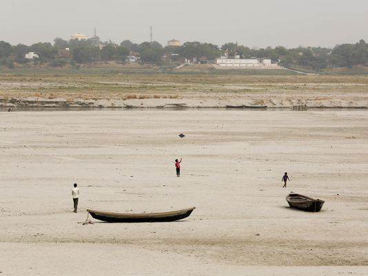 Indian children play near parked boats on the banks of river Ganges where water level has dried up in the summer in Allahabad, India, on June 3, 2015. Photo: Rajesh Kumar Singh, AP
