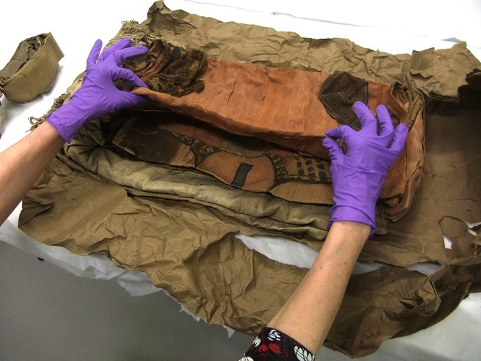 The shroud is removed from its package by conservators at National Museums Scotland.