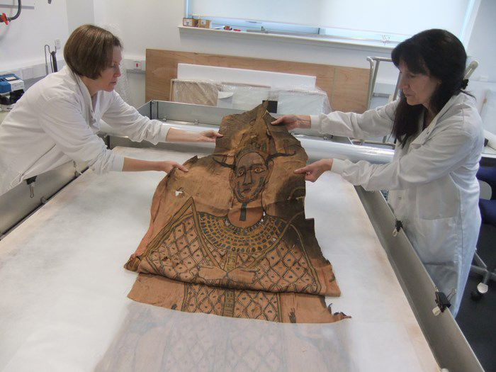 The shroud is unfolded by textile conservators at National Museums Scotland.