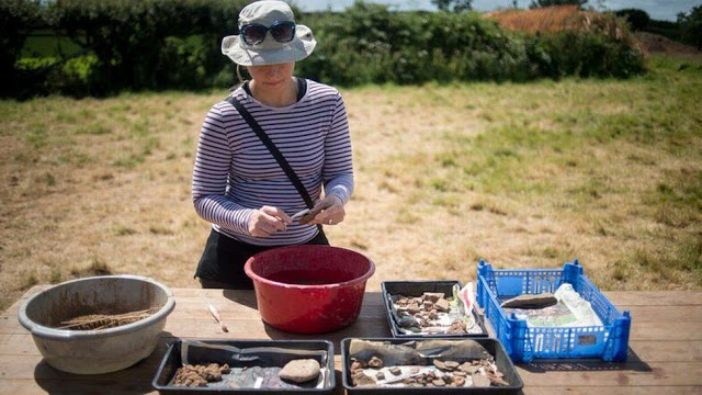 Archaeologist washing evidence of the iron works and pottery. Credit: University of Exeter.