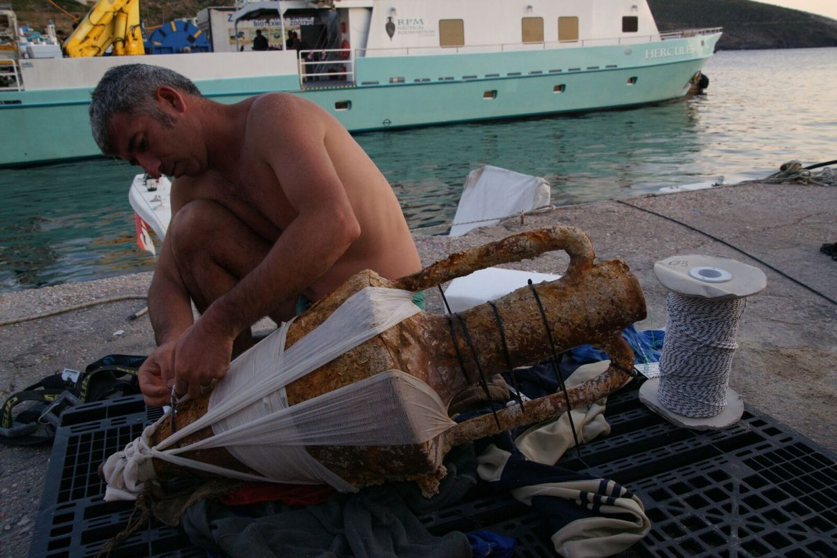 The chief conservator carefully prepares a Classical Period Chian amphora for the conservation tank. Photo by Vasilis Mentogianis. Credit: Ephorate of Underwater Antiquities-Hellenic Ministry of Culture and Sports / RPM Nautical Foundation