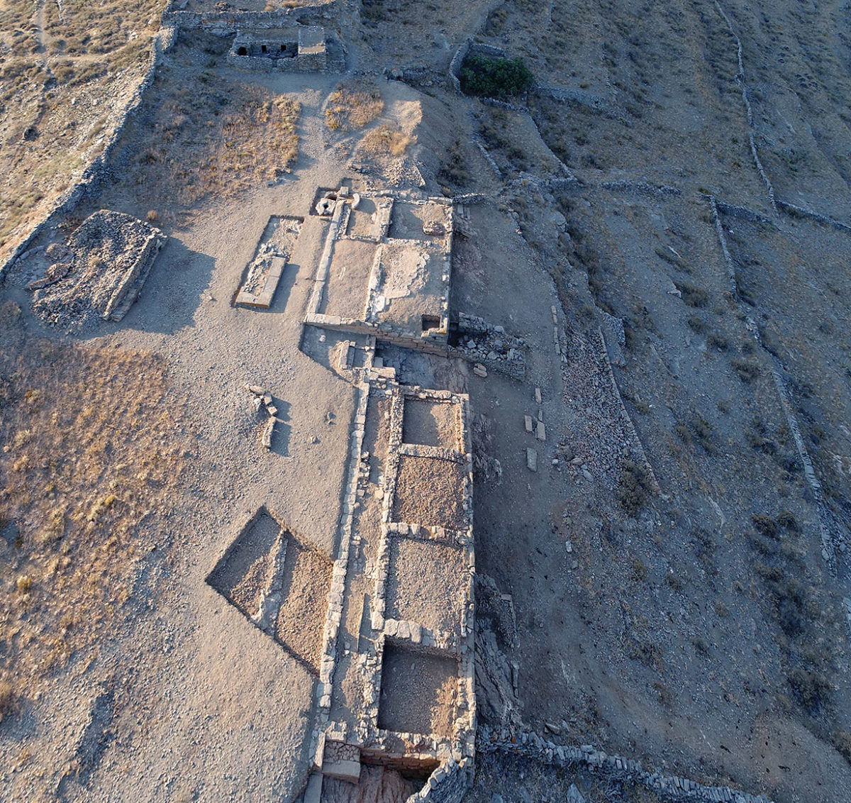 Fig. 17. Aerial photograph of the Ano Polis and Buildings 1 and 2 on the Middle Plateau, from the north. In the background the Acropolis with the sanctuary of Demeter. Photo Credit: Kostas Xenikakis.
