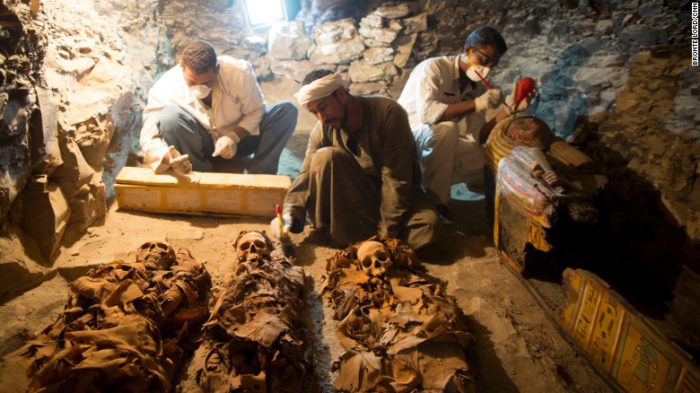 Researchers examine the tomb.