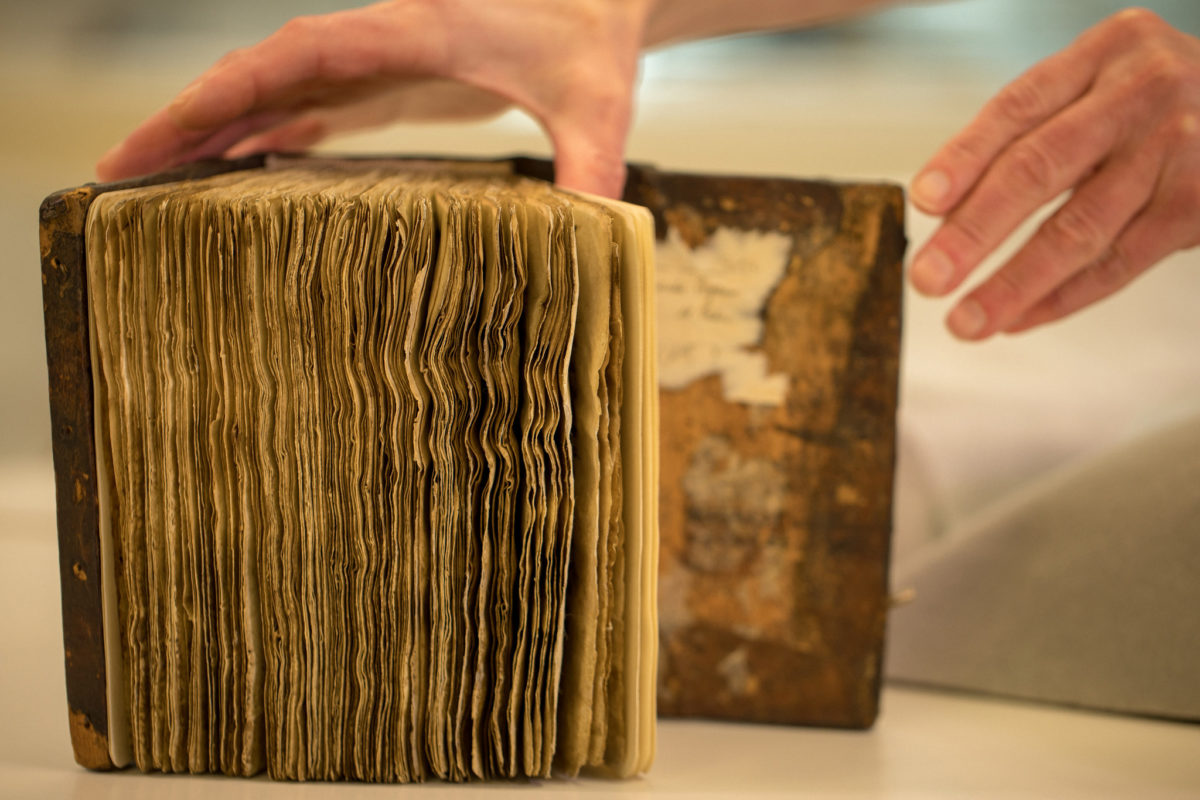 Conservators at Stanford University Libraries removed the pages from the leather-bound cover of the book of hymns, and mounted each leaf in an individually fitted, archival mat. (Farrin Abbott / SLAC National Accelerator Laboratory)