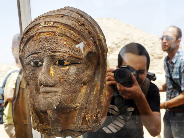 A photographer films a gilded mask found on the face of the mummy  of the second priest of Mut. Credit: Amr Nabil/AP