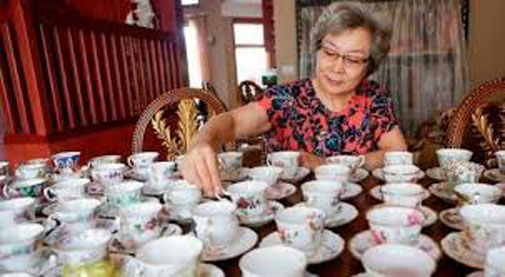 June Gao stands proudly in front of her dining room table in Canada which is covered with English china tea cups and saucers.
