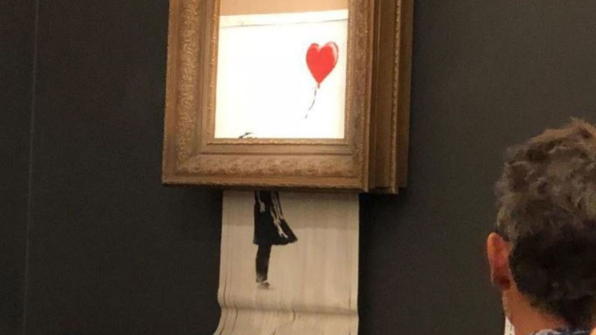 """The """"Girl with Balloon"""" was in fact torn into strips by a paper shredder attached by the artist to the back of the frame, but these pieces of the painting are now considered as a new work that Banksy himself has named """"Love is in the Bin."""""""