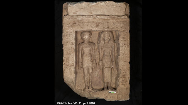 Limestone stela showing a man and woman standing next to each other. Their faces and names show  signs of deliberate damage inflicted in ancient times, making it difficult to read their names. Credit: GM and HMD - Tell Edfu Project 2018.
